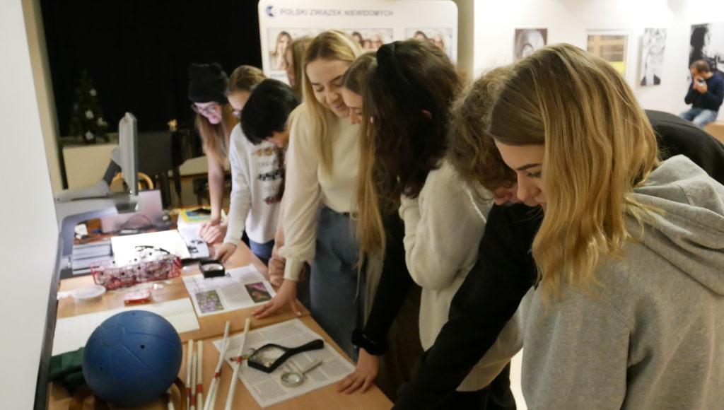 Uczestnicy warsztatów oglądają urządzenia i pomoce dla niewidomych