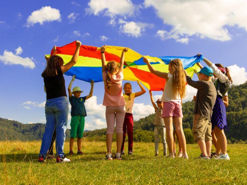 Dzieci bawią się kolorową płąchtą