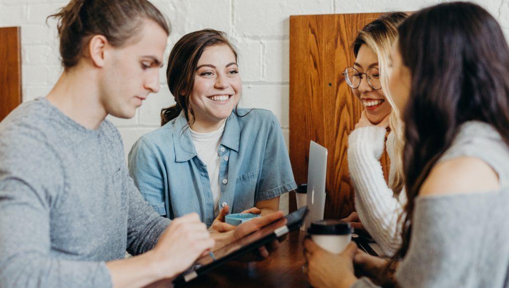 Kilka młodych osób rozmawia ze sobą przy stole