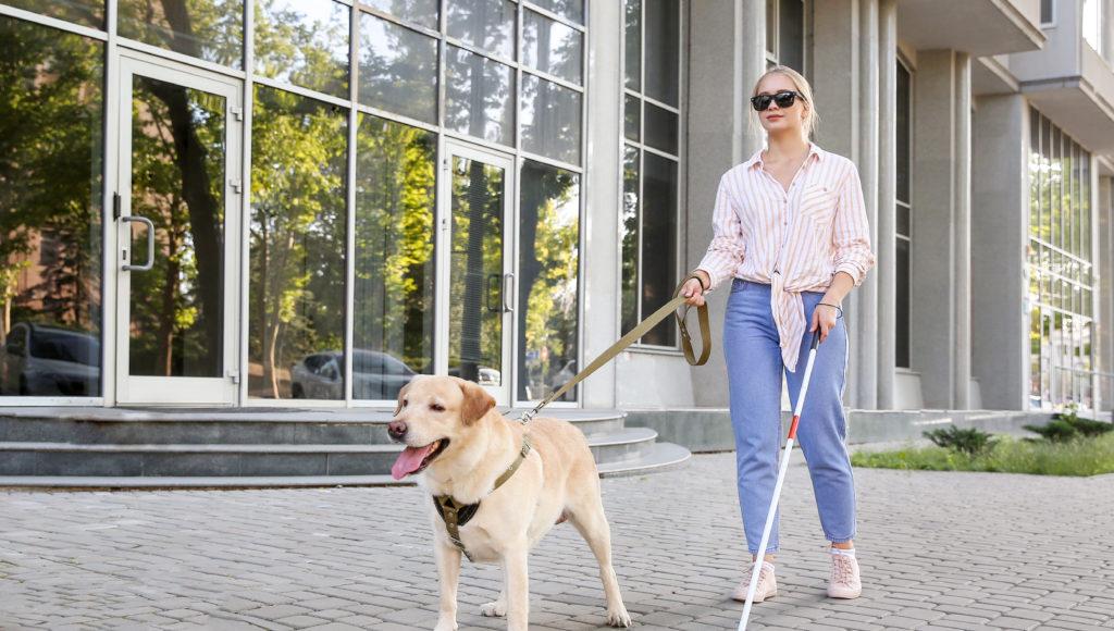 Niewidoma młoda kobieta przechodzi obok budynku