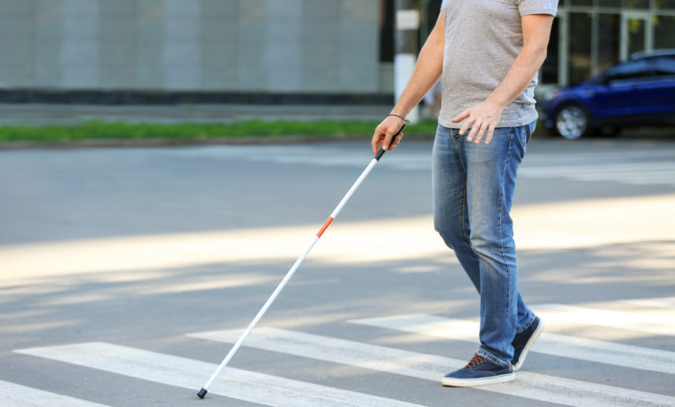 Mężczyzna z białą laską przechodzi przez przejście dla pieszych
