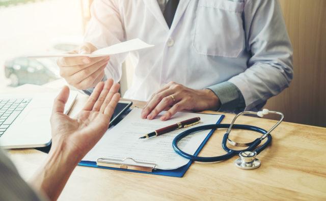 Lekarz przekazuje receptę pacjentowi