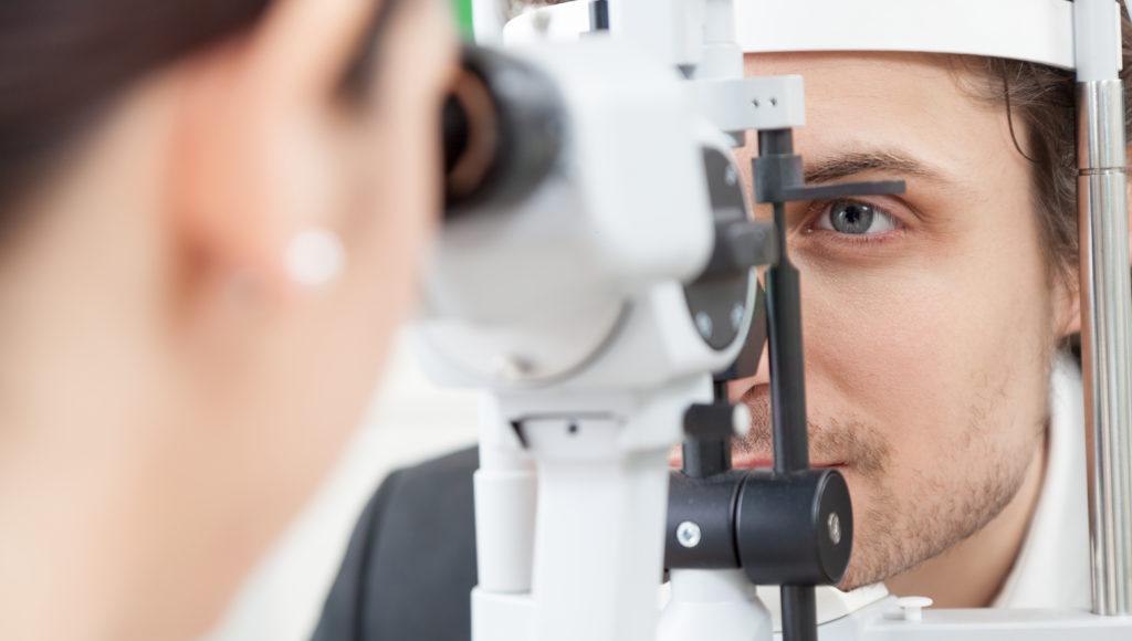 Lekarz bada oko pacjenta używając do tego specjalnego przyrządu