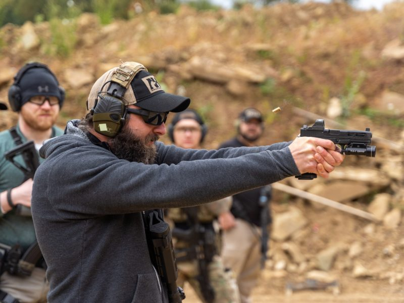 ężczyzna w czarnych okularach strzela z broni pneumatycznej w trakcie zajęć na strzelnicy