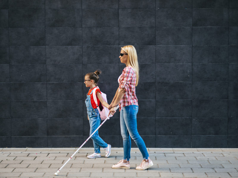 Kobieta niewidoma idzie drogą razem z małą dziewczynką