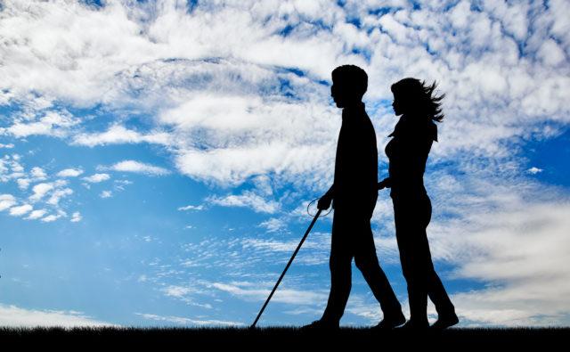Cień mężczyzny z białą laską idącego za rękę z kobietą, w tle niebo