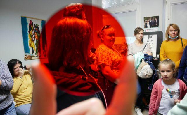 Zbliżenie na okrągły czerwony filtr medyczny, który pokazuje, jak zmienia się postrzeganie kolorów, gdy się go używa.
