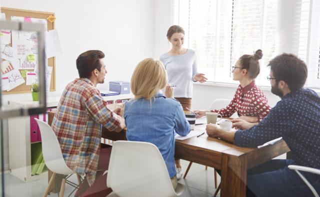 Młodzi ludzie siedzą przy stole i omawiają działania