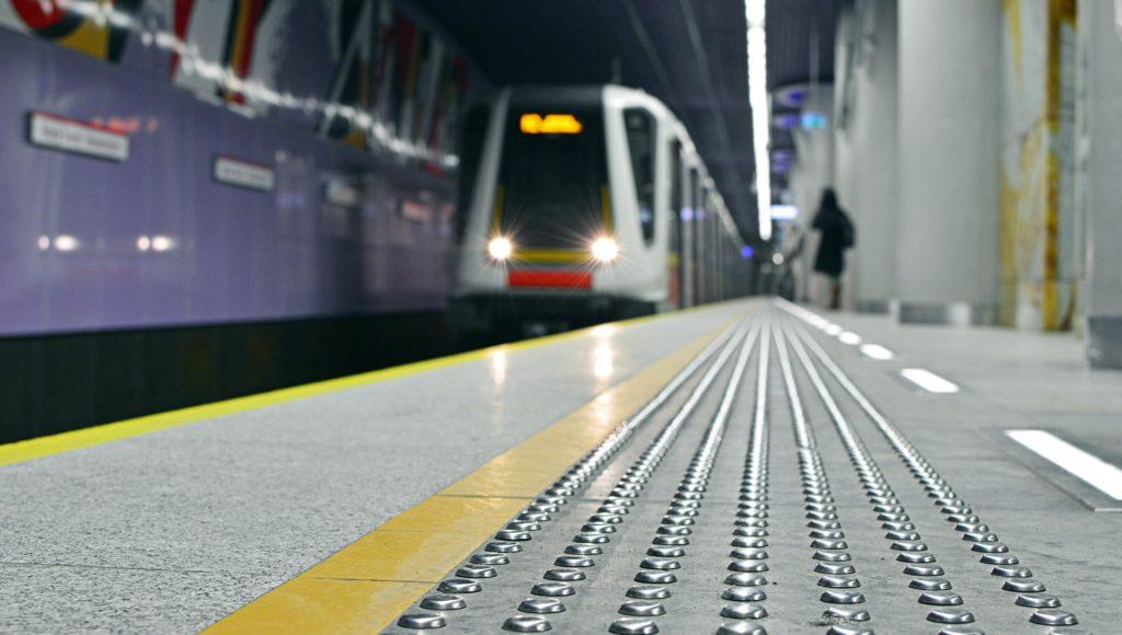 Pociąg metra wjeżdża na stację, widać ścieżkę dotykową dla osób niewidomych