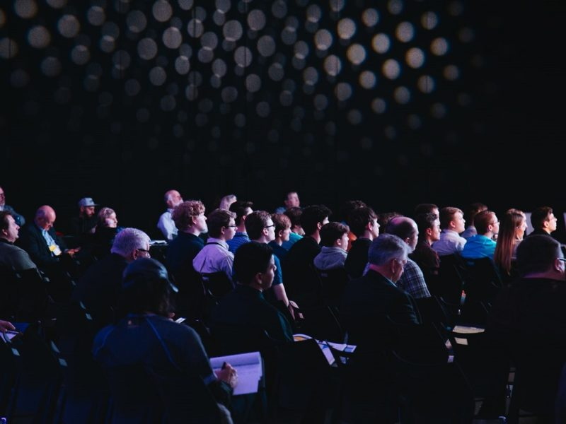 Uczestnicy spotkania, siedzą na sali z notatnikami