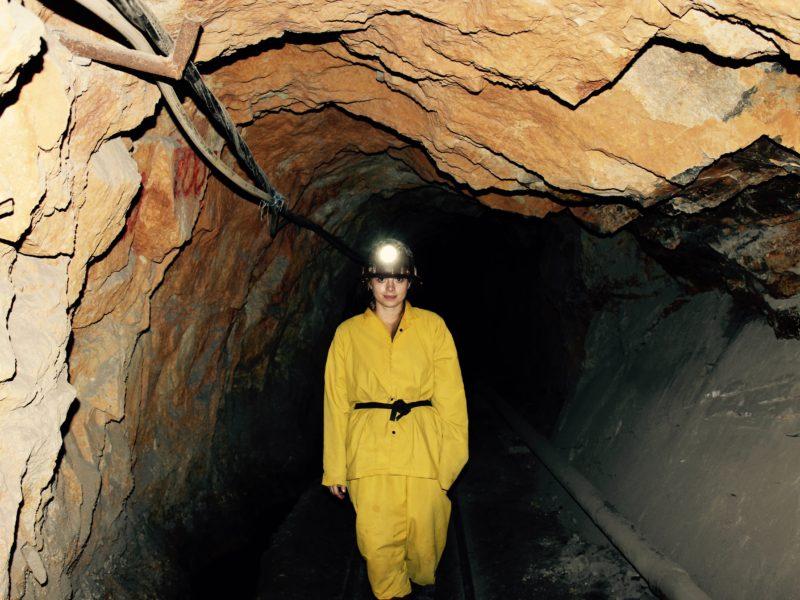 Kobieta w ubraniu górniczym idzie korytarzem kopalni